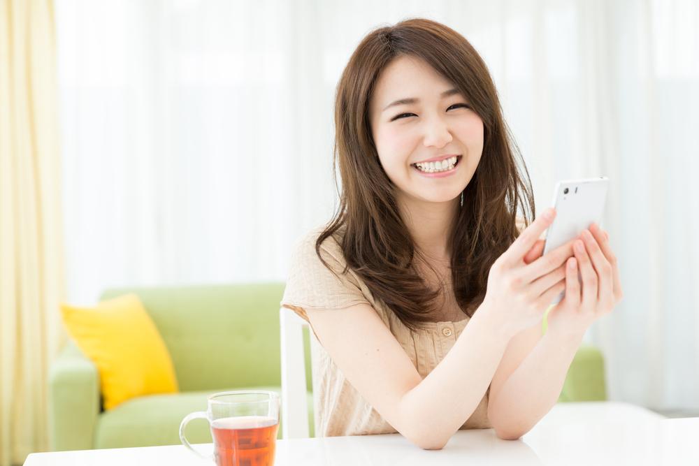 スマホを手に笑顔の女性