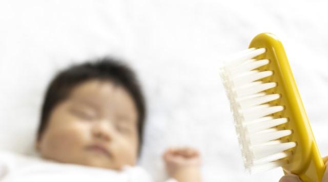 眠る赤ちゃんとヘアブラシ