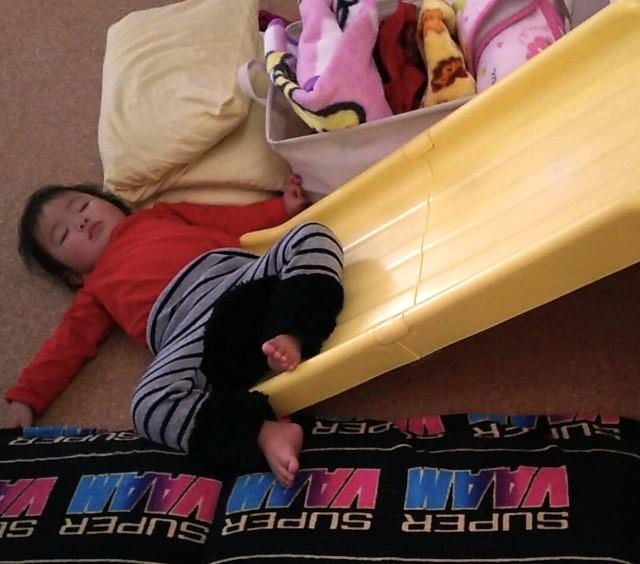 滑り台で遊びながら寝る子ども